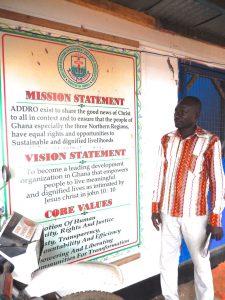 Emmanuel standing in front of sign